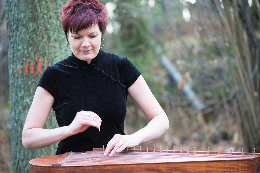 Pauliina Syrjälä soittaa Jooseppi Pohjolan kanteletta perinteisellä soittovälineellä.